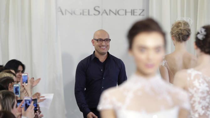 Designer Angel Sanchez greets the crowd during his 2013 bridal show in New York, Monday, April 22, 2013. (AP Photo/Seth Wenig)