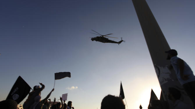 A Libyan military helicopter flies over a demonstration by Ansar al-Shariah Brigades and other Islamic militias, at Victory Square, in Benghazi, Libya, Friday, Sept. 21, 2012. The attack that killed the U.S. ambassador and three other Americans has sparked a backlash among frustrated Libyans against the heavily armed gunmen, including Islamic extremists, who run rampant in their cities. More than 10,000 people poured into a main boulevard of Benghazi, demanding that militias disband as the public tries to do what Libya's weak central government has been unable to.(AP Photo/Mohammad Hannon)