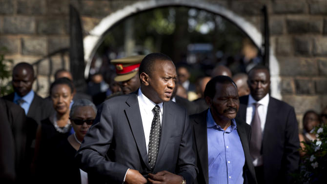 FILE - In this Friday, Sept. 27, 2013 file photo, Kenya's President Uhuru Kenyatta, center-left, arrives for the burial ceremony of his nephew Mbugua Mwangi and Mwangi's fiancee Rosemary Wahito, who were both killed in the Westgate Mall terrorist attack, at the burial site in the village of Ichawara, Kenya. A new poll released Thursday, Nov. 14, 2013 by Ipsos Synovate says two out of three people in Kenya want to see their president report to the International Criminal Court to respond to charges of crimes against humanity. (AP Photo/Ben Curtis, File)