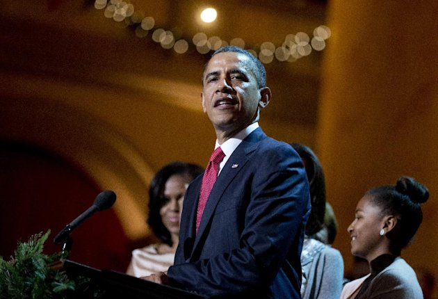 President Barack Obama delivers his remarks during the Annual Christmas in Washington presentation at the National Building Museum in Washington, Sunday, Dec. 9, 2012, surrounded by his family first lady Michelle Obama, left, and daughters Malia, obscured, and Sasha. (AP Photo/Manuel Balce Ceneta)