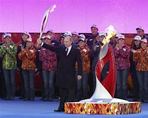 Russian President Putin holds a lighted Olympic torch during a ceremony to mark the start of the Sochi 2014 Winter Olympics torch relay in Moscow