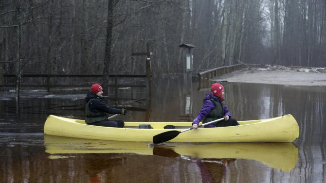 People canoe over a flooded road in Soomaa national park
