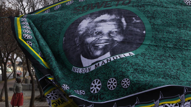 A woman walks behind a fabric bearing a portrait of former president Nelson Mandela in Soweto, South Africa Sunday June 9, 2013. Mandela has been hospitalized with an occurring lung infection. The latest government report says that he remains in a serious but stable condition. (AP Photo/Denis Farrell)