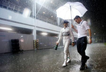 Mercedes Formula One driver Hamilton of Britain smiles as he walks with his assistant in the rain after qualifying for pole position in the Singapore F1 Grand Prix at the Marina Bay street circuit in Singapore