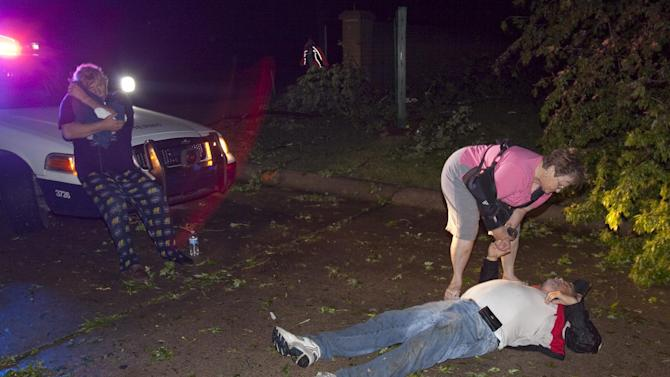 """Injured people gather at the entrance to a mobile home park in Wichita, Kan., after a tornado caused massive destruction in the area, on Saturday, April 14, 2012. Tornadoes were spotted across the Midwest and Plains on Saturday as an outbreak of unusually strong weather seized the region, and forecasters sternly warned that """"life-threatening"""" weather could intensify overnight. (AP Photo/The Wichita Eagle, Travis Heying) MAGS OUT; TV OUT"""