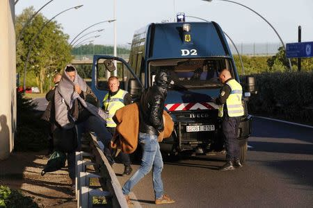 French gendarmes stand near as migrants hidden at the Eurotunnel site leave early in the morning in Calais