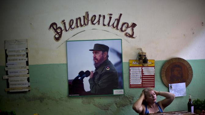 """A photograph of Fidel Castro hangs under the Spanish word """"Welcome"""" on the wall of a state-run food market in Havana, Cuba, Friday, Dec. 26, 2014. After the Dec. 17 announcement that Cuba and the U.S. would resume diplomatic relations for the first time since 1961, President Raul Castro, Fidel's brother, says he still wants an end to the trade embargo that has choked off commerce to the island. (AP Photo/Ramon Espinosa)"""