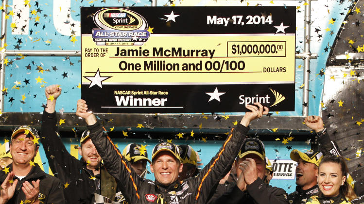 Jamie McMurray raises the mock check in Victory Lane after winning the NASCAR Sprint All-Star auto race at Charlotte Motor Speedway in Concord, N.C., Saturday, May 17, 2014. (AP Photo/Terry Renna)