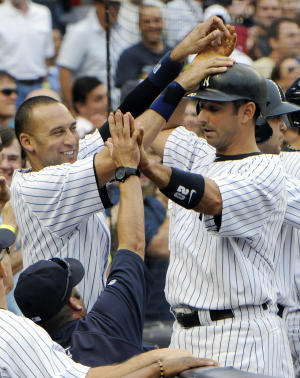 New York Yankees' Jorge Posada, right, high-fives with Derek Jeter and hitting coach Kevin Long, bottom left, after Posada's grand slam during the fifth inning of a baseball game against the Tampa Bay Rays, Saturday, Aug. 13, 2011, at Yankee Stadium in New York. (AP Photo/Bill Kostroun)