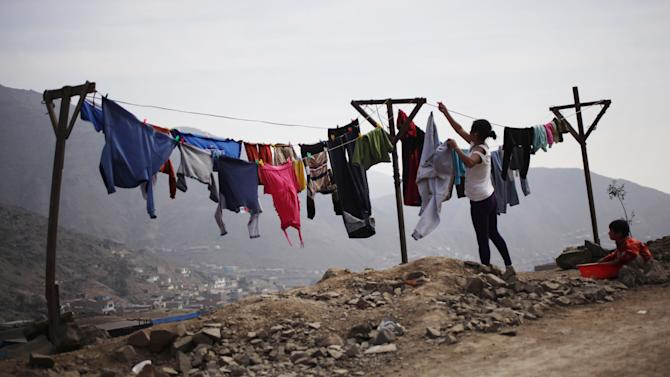 In this Oct. 19, 2012 photo, a woman hangs clothes on a line to dry in Comas on the outskirts of Lima, Peru. Seismologists, engineers and civil defense officials agree that Lima is due for an earthquake but is acutely vulnerable and sorely unprepared. More than two in five of capital residents inhabit rickety structures built on unstable, sandy soil and wetlands, which amplify a quake's destructive power, or in the hillside settlements ringing the capital that sprang up spontaneously over a generation as people fled conflict and poverty in the interior, experts say.  (AP Photo/Rodrigo Abd)