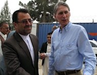 This file photo shows British Defence Secretary Philip Hammond (R), standing next to the Governor of Helmand Province, Gulab Mangal, in Lashkar Gah, in March. Hammond is considering bringing some British troops back from Afghanistan earlier than expected, he said in an interview published on Thursday