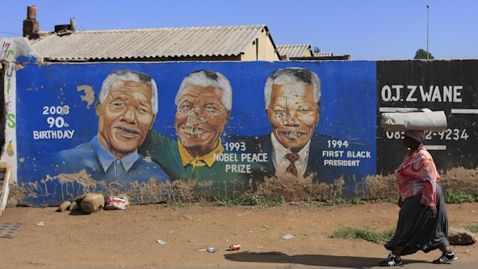 A woman walks past a mural showing former South African President Nelson Mandela in the Soweto area of Johannesburg, South Africa, on Sunday, Dec. 9, 2012. South Africa's presidency says that Mandela, 94, was admitted to a hospital Saturday in the nation's capital for tests. (AP Photos/Jon Gambrell)