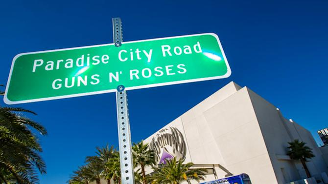 """This Monday Oct. 29,2012 photo provided by Erik Kabik shows the street sign after a ceremonial street renaming of Paradise Road to Paradise City Road in Las Vegas.  A county commissioner in Las Vegas says she regrets the board temporarily renamed a street in honor of Guns N' Roses after finding out about the band's suggestive publicity artwork. Ads promoting the band's four-week run at the Hard Rock Hotel & Casino depict a disheveled woman who appears to be sexually assaulted beneath the iconic """"Welcome to Fabulous Las Vegas"""" sign. (AP Photo/Courtesy Erik Kabik)"""