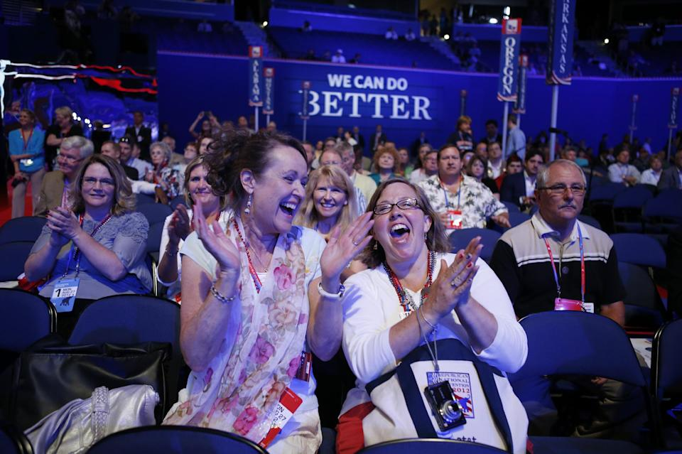 Ingrid Fuhriman from Bellevue, Wash., and Natalie Lavering from Lake Stevens, Wash., cheer as they watch a video presentation during an abbreviated session of the Republican National Convention in Tampa, Fla., on Monday, Aug. 27, 2012. (AP Photo/Jae C. Hong)