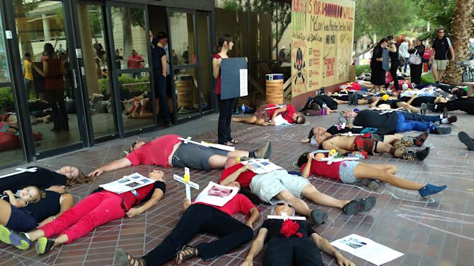 People lie on the sidewalk simulating a crime scene to symbolize the death of over 2,200 migrants in the desert over the last 20 years during a protest outside the office of Sen. John McCain, R-Ariz., in Tucson, Arizona, Wednesday, July 17, 2013. (AP Photo/Valeria Fernandez)