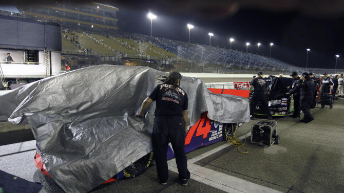 A crew member covers the truck of driver Mike Harmon (74) before the start of the NASCAR Ford 200 Truck series auto race at Homestead-Miami Speedway in Homestead, N.C., Friday, Nov. 18, 2011. (AP Photo/J Pat Carter)