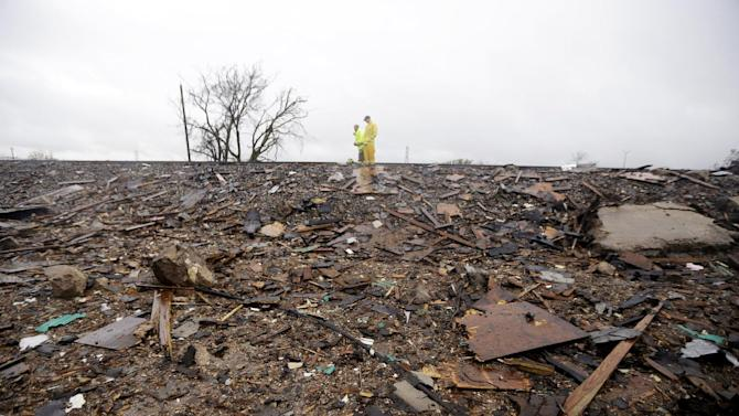 Firefighters stand on a rail line and survey the remains of a fertilizer plant destroyed by an explosion in West, Texas, Thursday, April 18, 2013.  A massive explosion at the West Fertilizer Co. killed as many as 15 people and injured more than 160, officials said overnight.  (AP Photo/LM Otero)