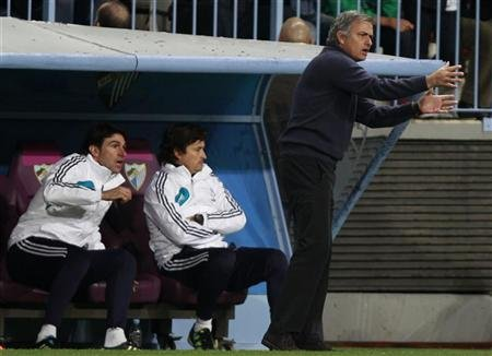 Real Madrid's coach Jose Mourinho (R) gestures during their Spanish First Division soccer match against Malaga at La Rosaleda stadium in Malaga December 22, 2012. REUTERS/Marcelo del Pozo