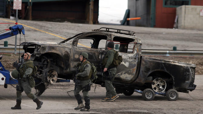 FILE - This Feb. 7, 2013 file photo shows a burned-out pickup truck belonging to ex-Los Angeles police officer Christopher Dorner being towed after it was discovered in Big Bear, Calif. (AP Photo/Jae C. Hong, File)