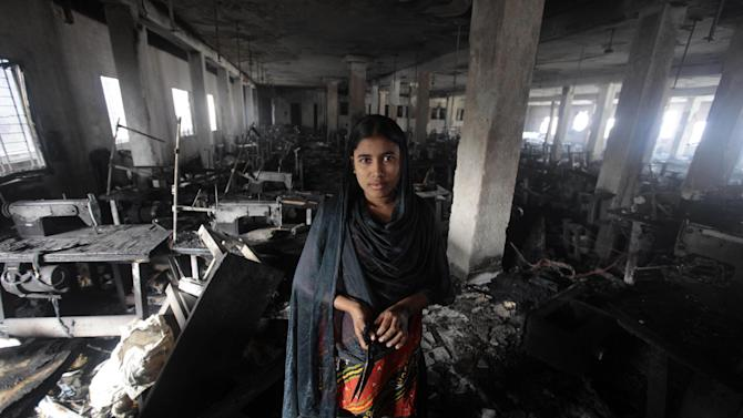 Bangladeshi garment worker Laiju stands inside the damaged Smart Export Garment Ltd. factory where a fire Saturday claimed the lives of seven of her female colleagues in Dhaka, Bangladesh, Sunday, Jan. 27, 2013. Bangladesh's government has ordered an investigation into allegations that the sole emergency exit at the factory was locked, an official said Sunday. Saturday's fire occurred just two months after a blaze killed 112 workers in another factory near the capital, raising questions about safety in Bangladesh's garment industry, which exports clothes to leading Western retailers. (AP Photo/A.M. Ahad)