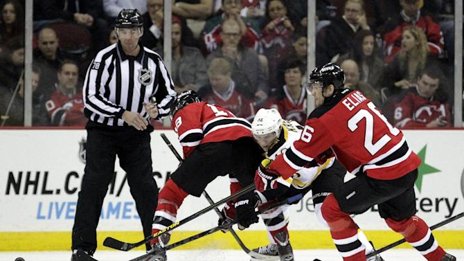 Boston Bruins center David Krejci, center, of the Czech Republic, competes for the puck with New Jersey Devils center Travis Zajac, left, and left wing Patrik Elias, of the Czech Republic, during the first period of an NHL hockey game, Wednesday, April 10, 2013, in Newark, N.J. (AP Photo/Julio Cortez)