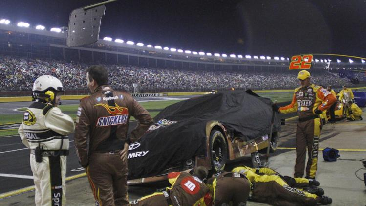 Kyle Busch, second from left, talks to a NASCAR official as crew members work on his car during a rain delay in the NASCAR All-Star auto race at Charlotte Motor Speedway in Concord, N.C., Saturday, May 18, 2013. (AP Photo/Nell Redmond)