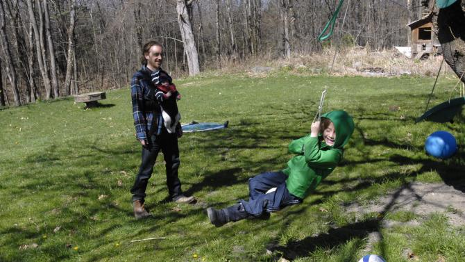 In this April 7, 2012 photo, Sayer Manning, 5, swings from a tree as his father, John and brother Fionn, three months, look on in the family's backyard in Chatham, N.Y.  The family continues to enjoy the outdoors, despite a large tick population in the region.  (AP Photo/Tim Roske)