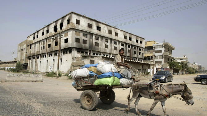 In this Friday, Oct. 19, 2012 photo, a Pakistani man rides a donkey-cart past a garment factory which was burnt last September, in Karachi, Pakistan. At the only morgue in Pakistan's largest city lie the blackened remains of 32 people killed in one of the worst industrial accidents in the country's history, wrapped in white plastic body bags waiting for DNA tests to determine who they are and where they belong. (AP Photo/Fareed Khan)