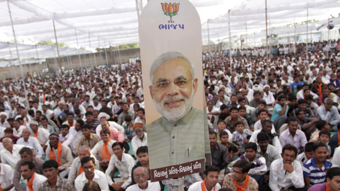 In this Monday, Dec. 3, 2012 photo, a placard featuring Gujarat Chief Minister Narendra Modi tied to a pole as people listen to his speech during an election campaign at Viramgam, Gujarat, India. Eleven years after Modi became the chief minister of the western state of Gujarat - and 10 years after brutal anti-Muslim rioting left over a 1,100 people there dead - Modi is campaigning for his third term. Nearly everyone expects him to be swept into office, and the top leadership of his rightwing Bharatiya Janata Party is already hailing him as a future prime minister. But few politicians in India are as polarizing as Modi. (AP Photo/Ajit Solanki)