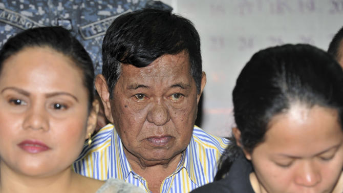 Andal Ampatuan Sr. , center, a powerful Filipino clan leader who is a suspect in the 2009 massacre of 57 people, listens during his arraignment on electoral sabotage at the Pasay city regional trial court, south of Manila, Philippines on Monday March 26, 2012. Andal Sr. has been on trial for murder and on Monday pleaded not guilty to charges of rigging elections to favor former President Gloria Macapagal Arroyo's allies. (AP Photo/Noel Celis, Pool)