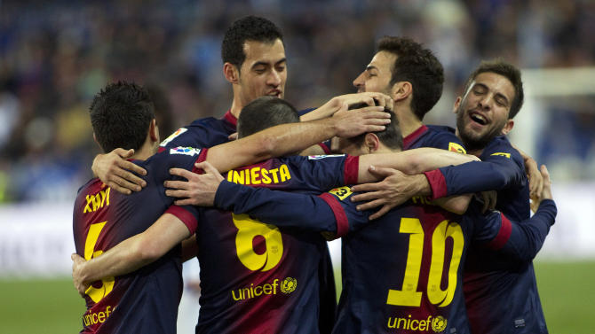 FC Barcelona's Lionel Messi from Argentina, second right, celebrates his goal with team mates during a Spanish La Liga soccer match against Malaga at the Rosaleda stadium in Malaga, Spain, Sunday, Jan. 13, 2013. (AP Photo/Julian Rojas Ocana)