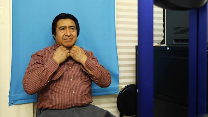 Luis Gordillo, a carpenter from Ecuador, adjusts his shirt collar as he has his picture taken while applying for a New York City municipal ID card at Make the Road New York in the Queens section of New York, Friday, Feb. 27, 2015. A municipal ID program that city officials thought would draw a few hundred thousand people in its first year has been much more popular than anticipated, with New Yorkers waiting hours in line and months for appointments to register. City officials have scrambled to keep up with the demand.  (AP Photo/Kathy Willens)