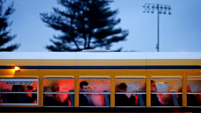 People arrive on a school bus at Newtown High School for a memorial vigil attended by President Barack Obama for the victims of the Sandy Hook Elementary School shooting, Sunday, Dec. 16, 2012, in Newtown, Conn. A gunman walked into Sandy Hook Elementary School in Newtown Friday and opened fire, killing 26 people, including 20 children. (AP Photo/David Goldman)