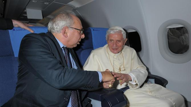 Rome Bureau Chief Victor Simpson, left, shakes hands with Pope Benedict XVI during the flight from Beirut to Rome, Sept. 16, 2012. Simpson has chronicled four papacies in 35 years covering the Holy See. A Vatican institution in his own right, Simpson has had a unique vantage point on history, enjoying the ear of Vatican insiders and chatting with the pope himself on foreign pilgrimages. (AP Photo/L'Osservatore Romano, ho)