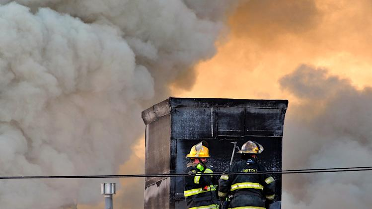 Firefighters battle a blaze that burned a fabric shop, upstairs apartments and a neighboring boutique in Philadelphia on Saturday, April 6, 2013. The fire caused a partial roof collapse that killed a firefighter and injured a colleague who was trying to rescue him, officials said. (AP Photo/Peter Tobia)