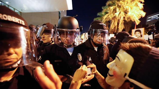 Protesters face off against a line of police during a demonstration outside LAPD headquarters