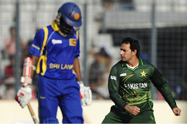 Pakistani bowler Saeed Ajmal (R) reacts after the dismissal of Sri Lankan batsman Upul Tharanga (L) during the one day international (ODI) Asia Cup cricket match between Pakistan and Sri Lanka at The
