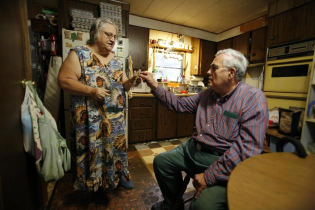 In this Sept. 15, 2011 photo, Judith Odyssey gets some help from her ex-husband Bill Ricker in the trailer home they share, in Hartford, Maine. They divorced around 1995 and she moved out. But he offe