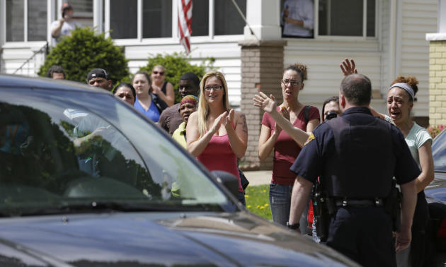Neighbors and friends of Amanda Berry clap as she arrives at her sister's home  Wednesday, May 8, 2013, in Cleveland. Berry, 27, Michelle Knight, 32, and DeJesus, had apparently been held captive in t