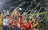Spanish players celebrate with the trophy after winning the Euro 2012 football championships final match Spain vs Italy at the Olympic Stadium in Kiev. Spain confirmed their status as one of the greatest national teams in football history by overwhelming Italy 4-0 in Sunday's Euro 2012 final in Kiev to retain their European crown