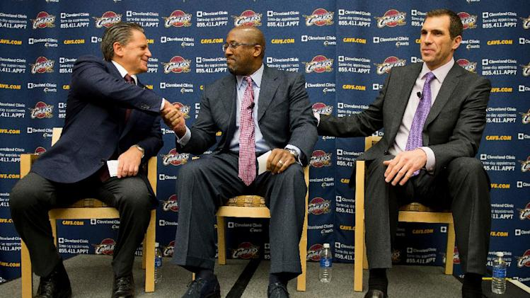 Cleveland majority owner Dan Gilbert, left, congratulates new head coach Mike Brown with general manager Chris Grant, right, during a press conference at the team's headquarters to introducing Brown on Wednesday, April 24, 2013, in Independence, Ohio. (AP Photo/Jason Miller)
