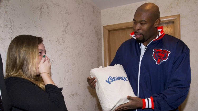 IMAGE DISTRIBUTED FOR KLEENEX - Chicago Bears standout defensive lineman Israel Idonije surprises Abby Owens with a hand-delivered Kleenex Care Pack on Wednesday, March 6, 2013 in Chicago. (John Konstantaras / AP Images for Kleenex)