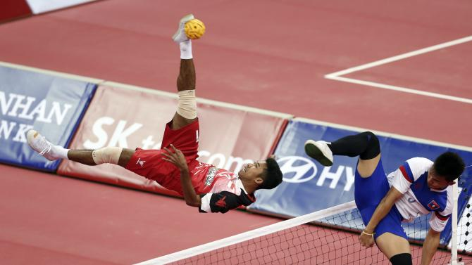 Indonesia's Syamsul Hadi strikes the ball as Laos' Noum Souvannalith defends during their men's doubles sepak takraw match at Bucheon Gymnasium during the 17th Asian Games in Incheon