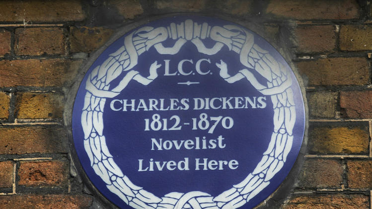 "FILE - In this Dec. 5, 2012 file photo, a blue plaque is seen on the exterior of Charles Dickens' home, part of the Charles Dickens Museum in London. For years, the four-story brick row house where the author lived with his young family was a dusty and slightly neglected museum, a mecca for Dickens scholars but overlooked by most visitors to London. Now, after a 3 million pound ($4.8 million) makeover, it has been restored to bring the writer's world to life. Its director says it aims to look ""as if Dickens had just stepped out."" (AP Photo/Sang Tan, File)"