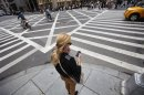 A woman uses her Apple iPhone while waiting to cross 5th Avenue in New York