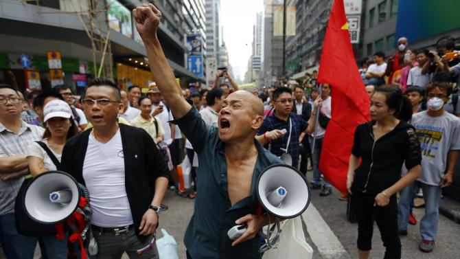Anti-Occupy protesters with megaphones and a Chinese flag express their anger as they come close to pro-democracy protesters' barricade at Mongkok shopping district in Hong Kong
