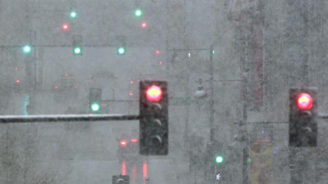 Pedestrians are shrouded in heavy snow as they cross a downtown street on Saturday, March 23, 2013, in Kansas City, Mo.  A winter storm warning is in effect for the area. (AP Photo/Charlie Riedel)