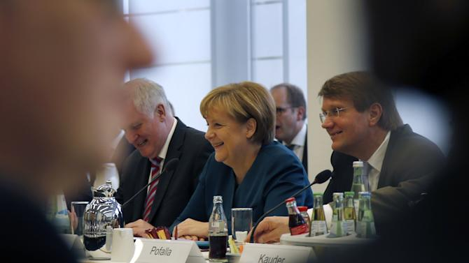 German Chancellor Angela Merkel, center, opens coalition talks with representatives of the Social Democrats in Berlin, Germany, Wednesday, Oct. 23, 2013. Merkel on Wednesday launched coalition negotiations with the main opposition Social Democrats, SPD, that are likely to set the stage for weeks of hard bargaining to form a new government. (AP Photo/Michael Sohn)