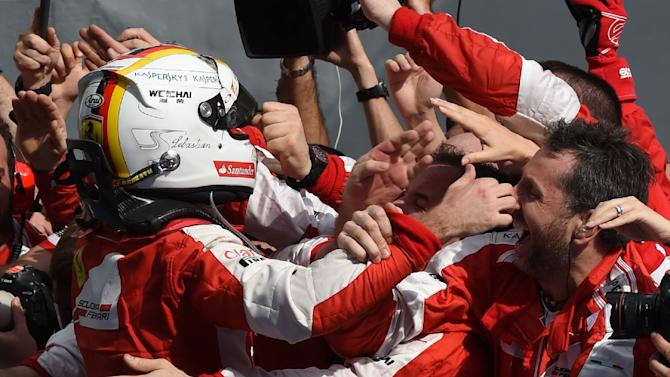 Sebastian Vettel (left) celebrates with team members after winning the Malaysian Grand Prix in Sepang on March 29, 2015