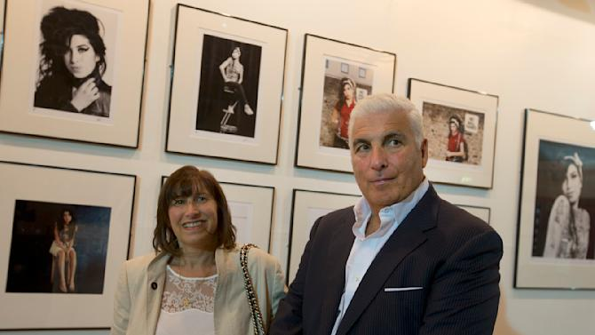 Janice and Mitch Winehouse mother and father of the late British singer Amy pose for the media, in front of portraits of their daughter at the Proud gallery in Camden, London, Wednesday, Sept.11, 2013. In the month she would have turned 30, Amy Winehouse is being celebrated in Camden the London neighbourhood that was her physical and spiritual home, she died of accidental alcohol poisoning at her house in July 2011, aged 27. The neighbourhood still attracts her fans, and local officials and businesses are holding a series of September events to raise money for the Amy Winehouse Foundation, a youth charity established by the singer's family. (AP Photo/Alastair Grant)